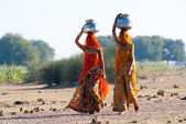 Women lugging a water pot on their head — Stock Photo