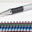 Stockfoto: Named ballpoint pen. On notebook into cell.