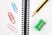 Notebook, pen, pencil sharpener and clip close-up. — Stock Photo