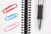 Notebook, pen and paper clips close up. — Стоковое фото