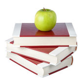 A stack of books and an apple. On a white background. — Stock Photo