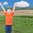 A boy in a landscape. With raised hands. — Stockfoto