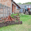 Antique tractor and plow on the farm. - Stock Photo