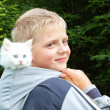 A boy and a white kitten in the hood. In nature. — Stock Photo