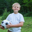 Boy football player with ball on nature. — Stock Photo