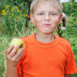 Boy eating apples in the garden. — Stock Photo