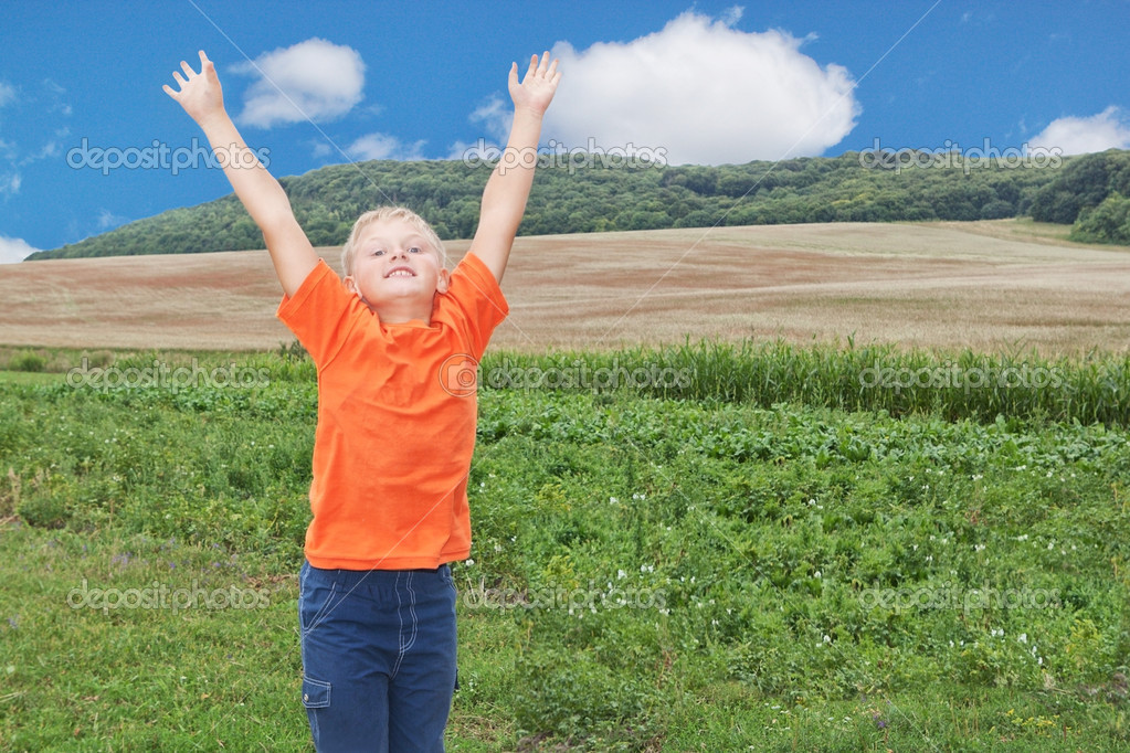 A boy in a landscape. With raised hands.  Stock Photo #12574453