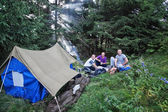 Friends in the campaign with a tent in the Carpathian forest. — Stock Photo