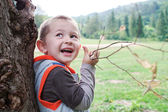 Boy child playing outdoors branch. — Stock Photo