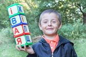 A boy holds a toy cubes with letters outside. — Stock Photo