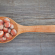 Hazelnuts for Christmas on a wooden spoon. - Stock Photo