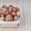 Basket with wood, walnuts and almonds. On a wooden texture. — Stock Photo #13635733