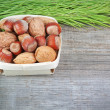 Christmas basket with wood, walnuts and almonds. On a wooden tex — Stock Photo #13635738