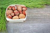 Vánoční košík s dřevem, vlašské ořechy a mandle. na dřevěné tex — Stock fotografie
