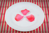 Arrangement of rose petals on a plate. On a red napkin. — Stock Photo