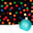 Stock Photo: Blue Christmas ball in the snow. On the background bokeh lights.
