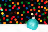 Blue Christmas ball in the snow. On the background bokeh lights. — Stock Photo