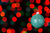 Christmas blue ball on the background of colorful bokeh. — Stock Photo