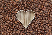 Heart shape in coffee beans on a wooden texture. — Stock Photo