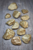 Gold nuggets scattered stones on wooden texture. — Stock Photo