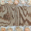 Straw Christmas snowflakes on a wooden texture in the frame. — Stock Photo