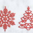 Decorative red Christmas tree and snowflake on white snow. — Stock Photo