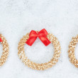 Three decorative Christmas wreath of straw closeup in the snow. - Stock Photo