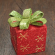 Christmas gift box with a bow on a wooden texture. - Foto de Stock
