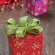 Christmas gifts with ribbons on wooden texture closeup. — Stock Photo