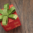 Christmas gift box with a bow on a wooden texture closeup. — Stock Photo