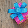 Christmas gift box with blue bow on a wooden texture closeup. — Stock Photo