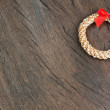 Straw Christmas wreath on a wooden texture. — Stock Photo
