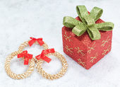Christmas gift box and decorative straw wreath. In the snow. — Stock fotografie