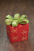 Christmas gift box with a bow on a wooden texture. — Stock Photo