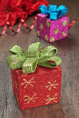 Christmas gifts with ribbons on wooden texture closeup. — Stockfoto