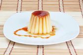 Yogurt-pudding on a plate on decorative wooden napkin. — 图库照片