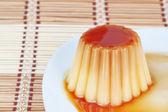 Close-up of yogurt pudding on a plate on decorative wooden napki — Stock Photo