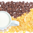 Cup of milk on a background corn flakes and chocolate flakes. — Stock Photo