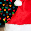 Christmas santa hat on a background of colored bokeh. — Stock Photo
