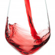 Red wine pouring into a crystal glass. On a white background. — Stock Photo