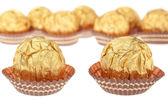 Group chocolate candies wrapped in gold. On a white background. — Stok fotoğraf