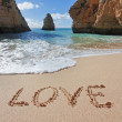 Word love in the sand at the beach on Valentine - Stock Photo