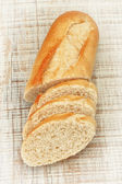 Sliced ​​pieces of fresh bread on the board texture. Close-up. — Foto de Stock