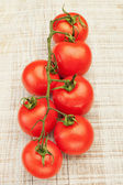 Large bunch of juicy red tomatoes on the board. — Stock Photo