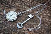 Silver pocket watch and key on wooden texture. — Stock Photo