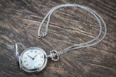 Silver pocket watch on chain, a wooden texture. — Stock Photo