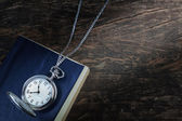 Pocket watch on an old book, a notebook. — Stock Photo