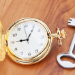Gold pocket watch and key. Against the background of a wooden te — Stock Photo