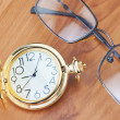 Gold pocket watch and glasses on a wooden background texture — Stock Photo