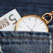 Stock Photo: Pocket watch with chain in jeans and five euros. Close-up.